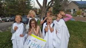 students dressed in Greek chitons gesturing dramatically